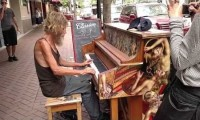 Bezdomny mężczyzna gra na pianinie