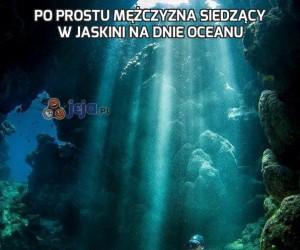 Po prostu mężczyzna siedzący w jaskini na dnie oceanu