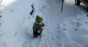 Szympans w stroju dziecka bawi się na śniegu