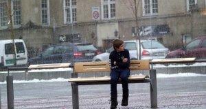 Zmarznięty chłopiec na przystanku