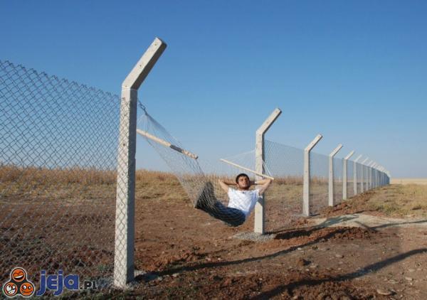 Człowiek wylegujący się na zgiętym fragmencie metalowego ogrodzenia.