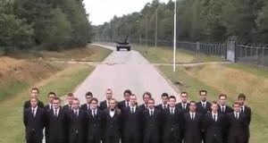 Ustawieni w szeregu przed nadjeżdżającym czołgiem